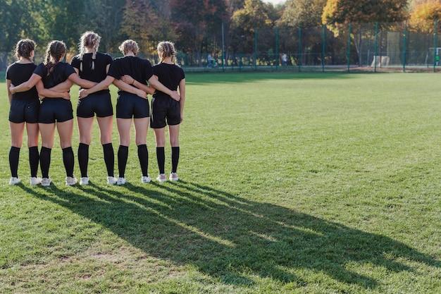 Achteraanzicht meisjes staan in een voetbalveld Gratis Foto
