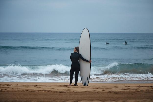 Achteraanzicht op mooie jonge surf meisje haar longboard knuffelen op de kust van de oceaan en kijken naar golven voor het surfen Gratis Foto