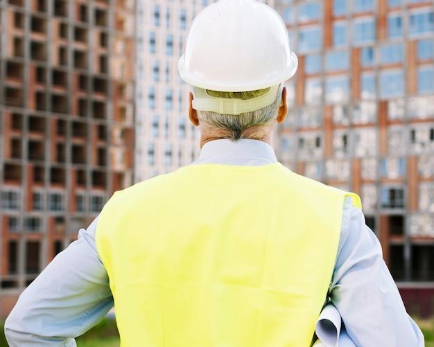 Achteraanzicht oude man met helm Gratis Foto