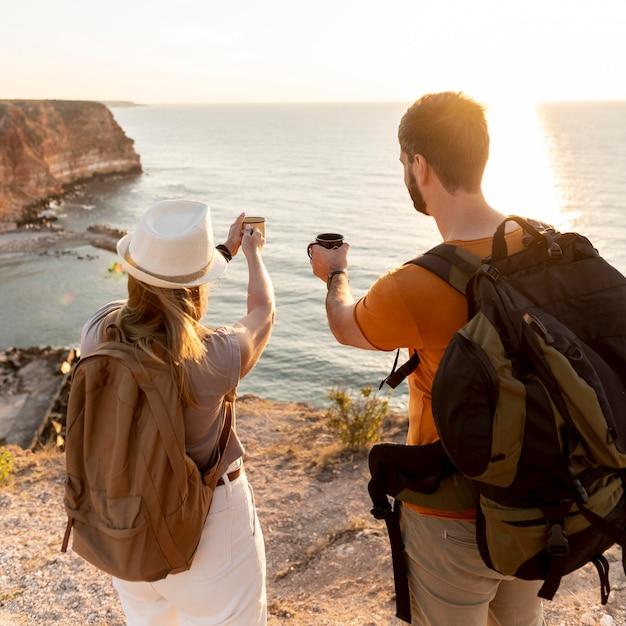 Achteraanzicht paar genieten van een kopje koffie bij zonsondergang Gratis Foto