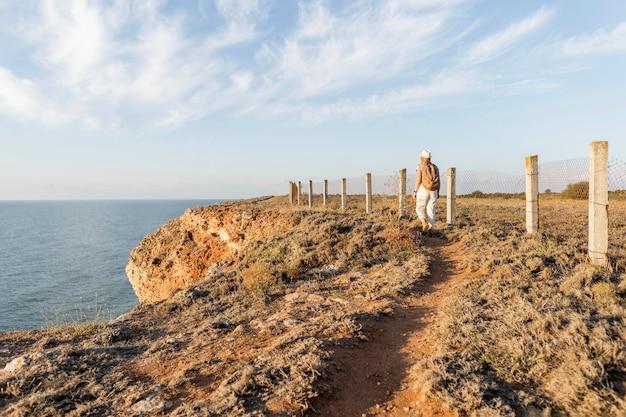 Achteraanzicht persoon lopen op een kust Gratis Foto