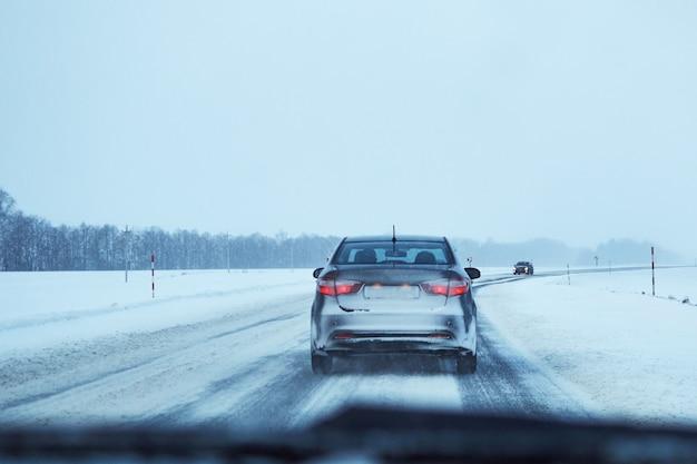 Achteraanzicht van auto op besneeuwde winter weg Premium Foto
