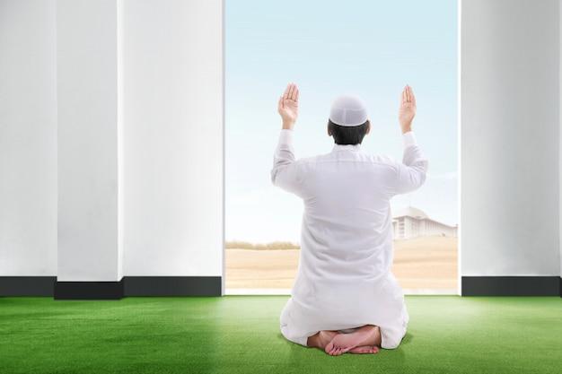 Achteraanzicht van aziatische moslim man zitten in biddende positie op het tapijt steek de hand en staren de hemel vanuit de kamer Premium Foto