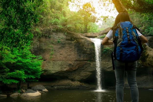 Achteraanzicht van aziatische vrouw met rugzak kijken naar kleine waterval in de jungle. Premium Foto