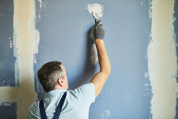 Achteraanzicht van de hoge sectie van senior bouwvakker droge muur gladstrijken tijdens het renoveren van huis, kopieer ruimte Premium Foto