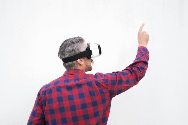 Achteraanzicht van de mens in vr-headset wijzend met vinger Gratis Foto