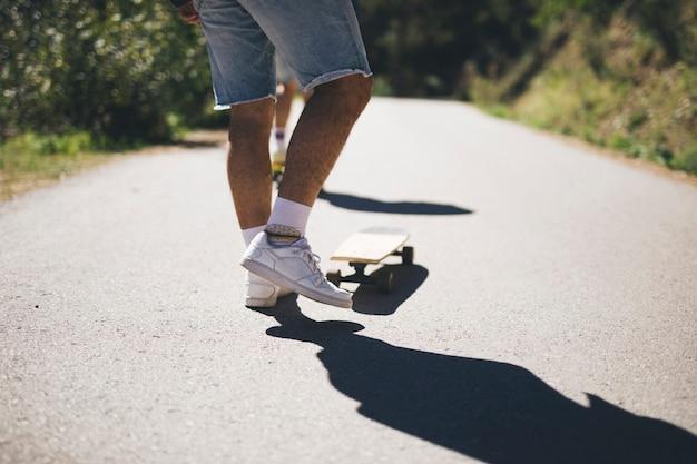 Achteraanzicht van de mens op skateboard Gratis Foto