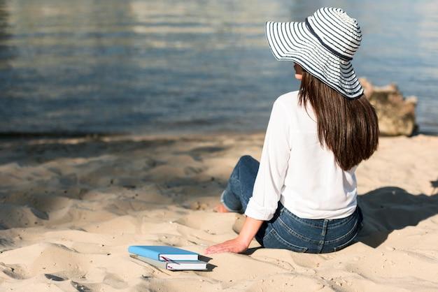 Achteraanzicht van de vrouw die het uitzicht vanaf het strand bewondert Gratis Foto