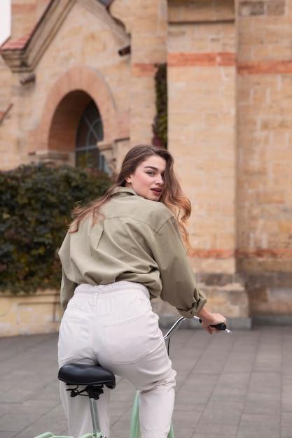 Achteraanzicht van de vrouw fietsten in de stad Gratis Foto