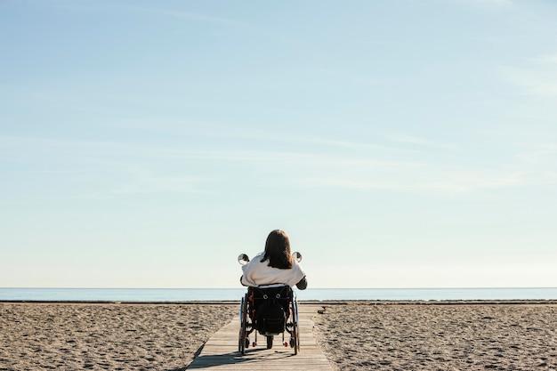 Achteraanzicht van de vrouw in een rolstoel op het strand Gratis Foto