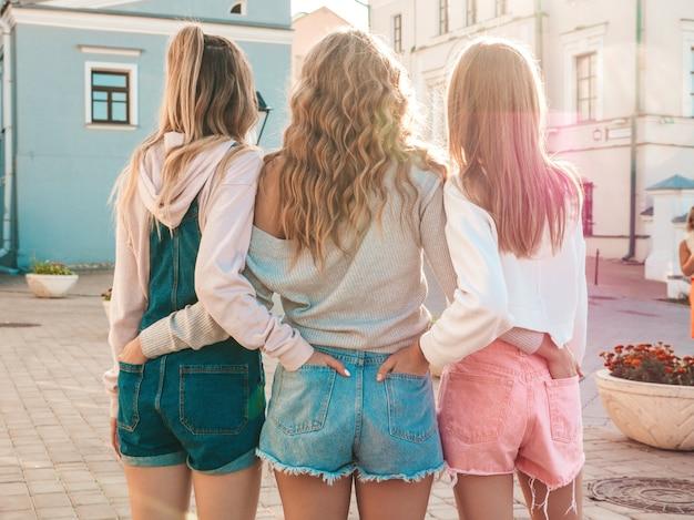 Achteraanzicht van drie jonge vrouwelijke hipster vrienden. meisjes gekleed in zomer casual kleding. vrouwen buitenshuis staan. ze staken hun handen in korte broek in achterzakken. poseren bij zonsondergang Gratis Foto