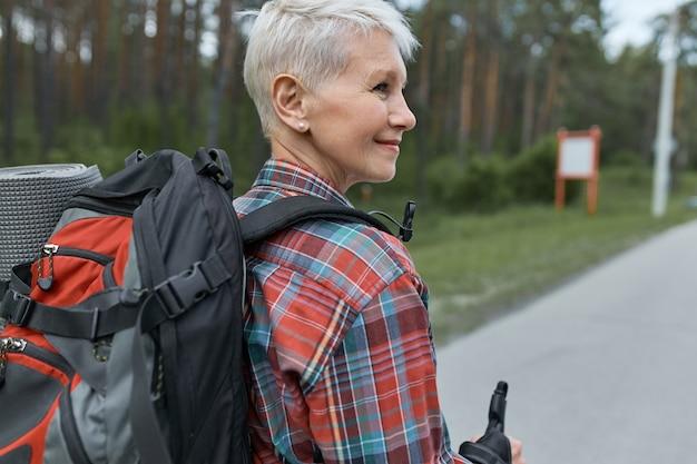 Achteraanzicht van een avontuurlijke vrouw van middelbare leeftijd met een pixiekapsel die rugzak draagt tijdens het wandelen, weekenden in de bergen gaat doorbrengen. Gratis Foto