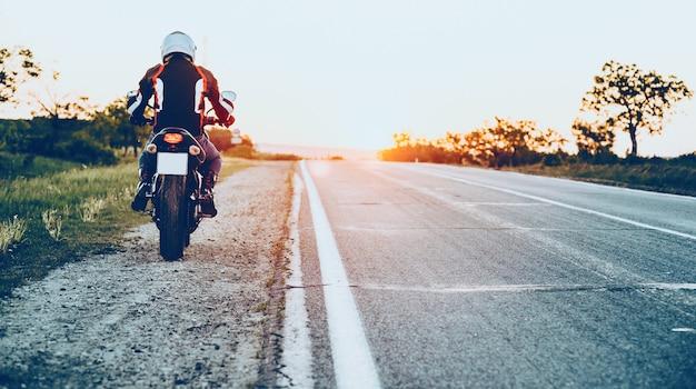 Achteraanzicht van een blanke man die goed uitgerust begint te rijden op een motorfiets met een zonsondergang op de achtergrond Premium Foto