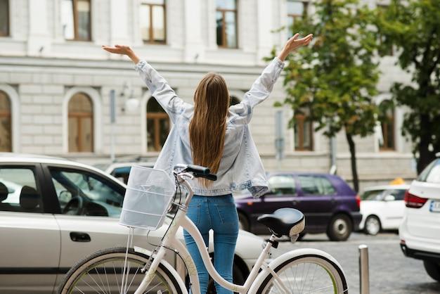 Achteraanzicht van een gelukkige vrouw met fiets Gratis Foto