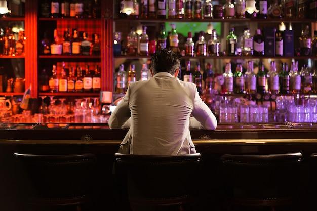 Achteraanzicht van een jonge man bier drinken Gratis Foto