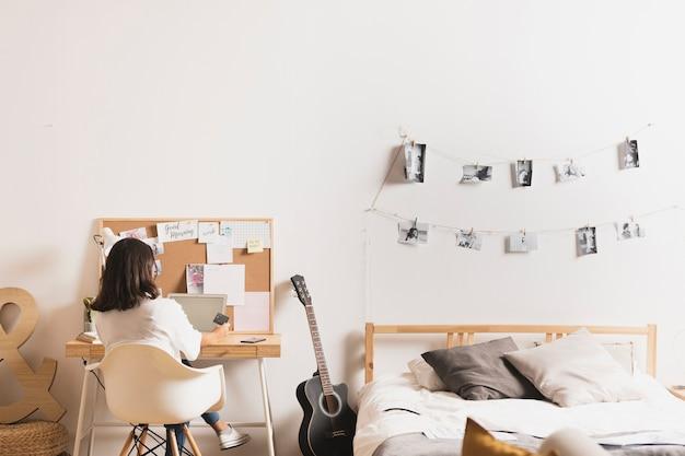 Achteraanzicht van een jonge vrouw die thuis werkt Gratis Foto