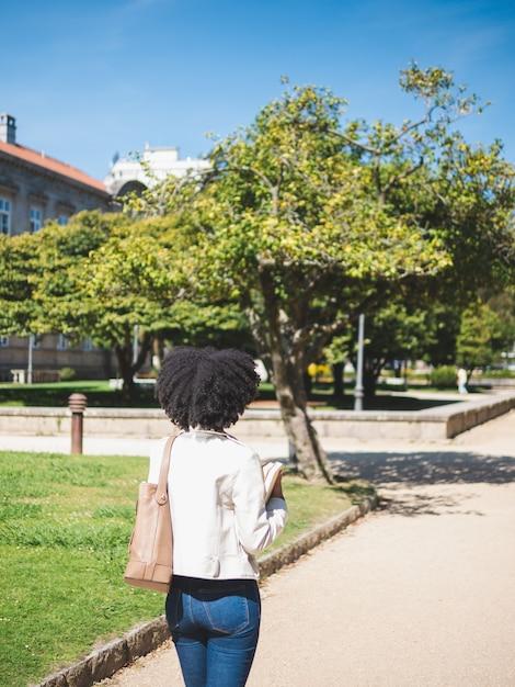 Achteraanzicht van een jonge zwarte vrouw, met krullend haar, die enkele boeken buiten houdt Premium Foto