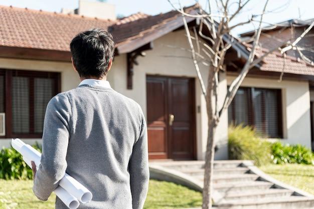 Achteraanzicht van een man die naar een huis kijkt Gratis Foto