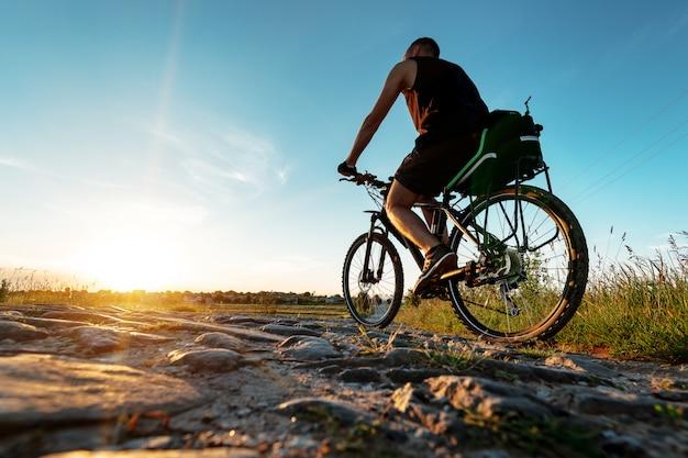 Achteraanzicht van een man met een fiets tegen de blauwe hemel. Premium Foto