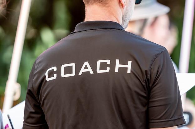 Achteraanzicht van een mannelijke coach draagt zwart coach shirt met het witte woord coach op de achterkant gedrukt Premium Foto