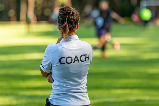 Achteraanzicht van een vrouwelijke sportcoach kijken naar haar team concurreren op een outdoor voetbalveld Premium Foto