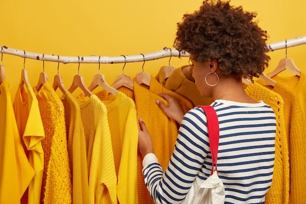 Achteraanzicht van gekrulde haired dame in gestreepte trui, draagtas, kleding kiest, gele trui op hangers oppikt. Gratis Foto