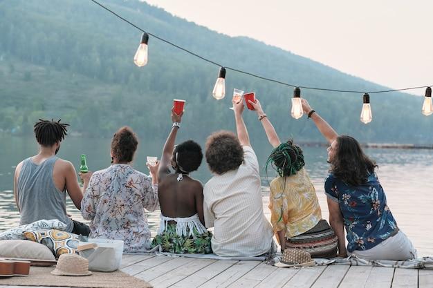 Achteraanzicht van groep vrienden roosteren met glazen bier en vieren hun zomervakantie zittend op een pier Premium Foto
