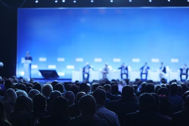 Achteraanzicht van het publiek over de sprekers op het podium in de conferentiezaal of seminarvergadering, bedrijfs- en onderwijsconcept Premium Foto