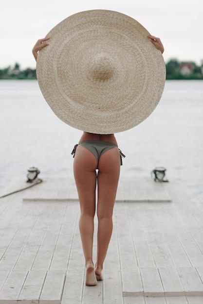 Achteraanzicht van jonge afro vrouw terug sexy zwembroek en grote zomer sombrero hoed Gratis Foto