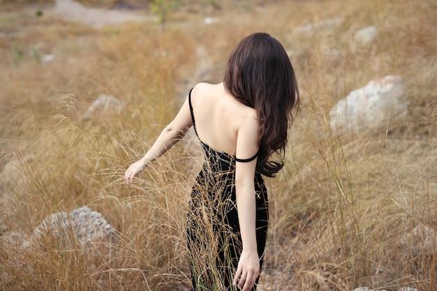 Achteraanzicht van jonge aziatische vrouw, lang haar in zwarte jurk lopen op berg onder droog gras met vreedzame Premium Foto