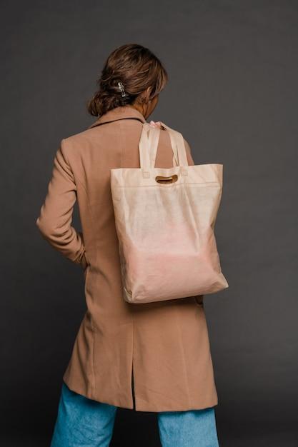 Achteraanzicht van jonge casual vrouw in elegante jas en spijkerbroek met textiel draagtas op schouder Premium Foto