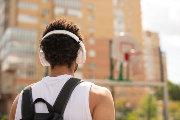 Achteraanzicht van jonge interculturele sportman met koptelefoon en rugzak staande op speelplaats in stedelijke omgeving Premium Foto