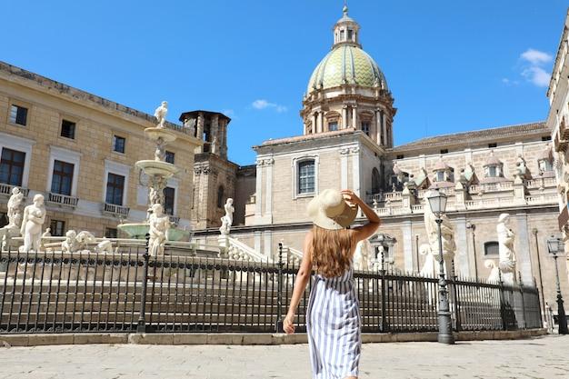 Achteraanzicht van jonge mooie vrouw wandelen in de buurt van de monumentale praetoriaanse fontein in palermo, italië. Premium Foto