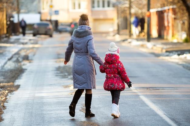 Achteraanzicht van jonge slanke aantrekkelijke vrouw moeder en klein kind meisje dochter in warme kleding lopen samen hand in hand glibberige straat oversteken op zonnige winterdag op onscherpe stedelijke achtergrond. Premium Foto