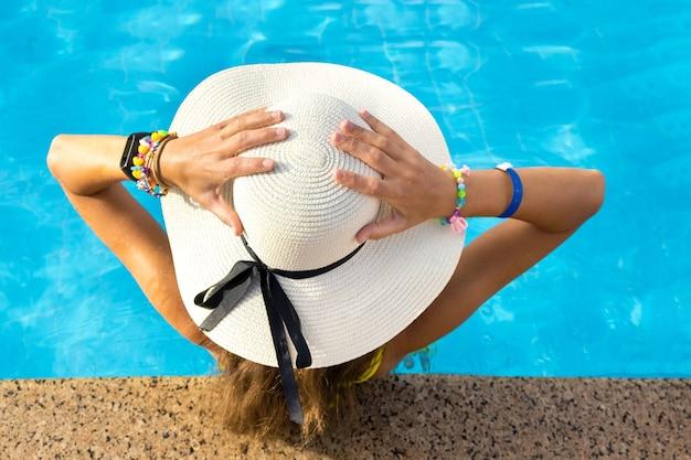 Achteraanzicht van jonge vrouw met lang haar dragen gele strooien hoed ontspannen in warme zomer zwembad Premium Foto