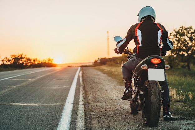 Achteraanzicht van man in beschermende jas, laarzen en helm rijden langs de weg bij zonsondergang op lege snelweg verlichte achtergrond Premium Foto