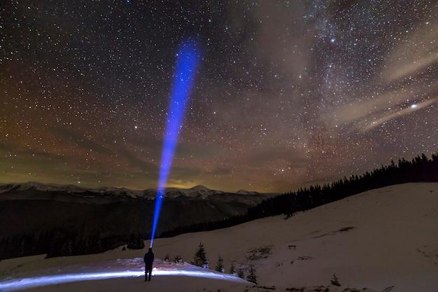 Achteraanzicht van man met hoofd zaklamp staande op besneeuwde vallei onder prachtige donkerblauwe winter sterrenhemel Premium Foto