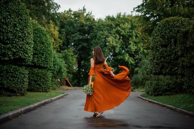 Achteraanzicht van mooie vrouw in lange oranje jurk lopen op de natte weg Premium Foto