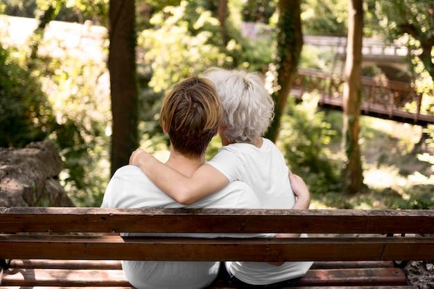 Achteraanzicht van omhelsde paar het uitzicht op het park vanaf de bank bewonderen Gratis Foto