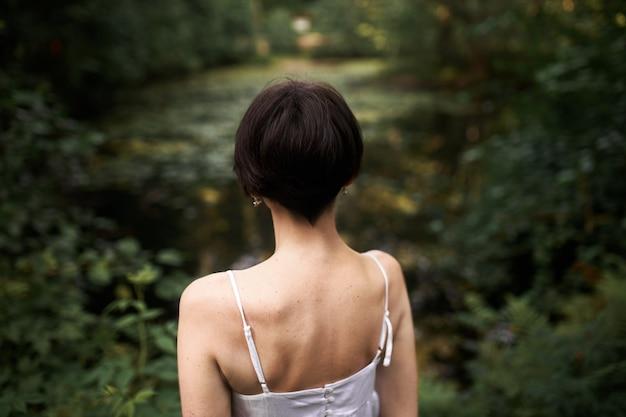 Achteraanzicht van onherkenbare jonge vrouw met kort haar en slank lichaam poseren buitenshuis, staande voor vijver met haar rug naar de camera. Gratis Foto