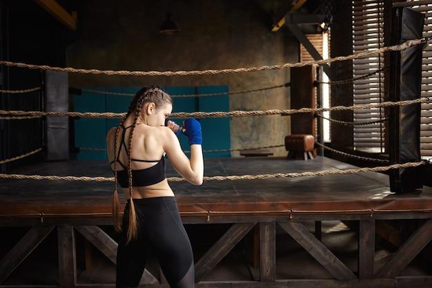Achteraanzicht van professionele vrouwelijke bokser met twee vlechten permanent in lege sportschool met boksring op achtergrond, alleen training Gratis Foto