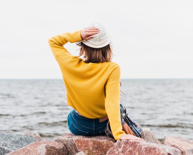 Achteraanzicht van reizende vrouw met uitzicht op de oceaan Gratis Foto