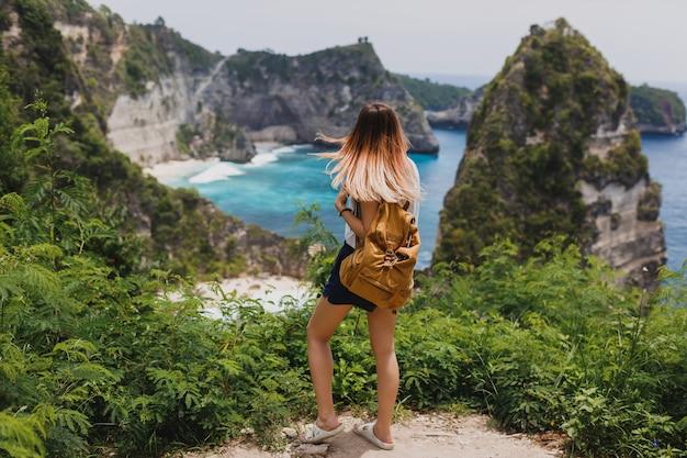 Achteraanzicht van reizende vrouw staande op kliffen en tropisch strand Gratis Foto