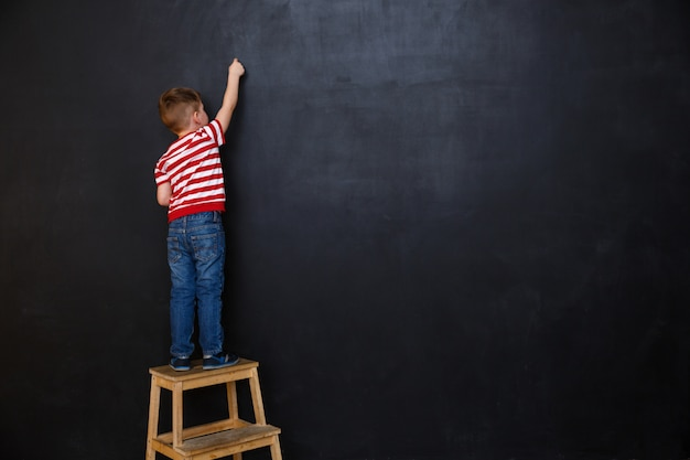 Achteraanzicht van schattige kleine jongen jongen schrijven met krijt Gratis Foto