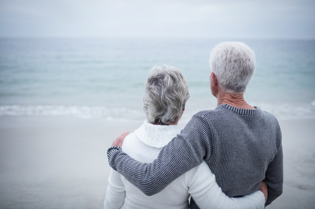 Achteraanzicht van senior paar omarmen op strand Premium Foto