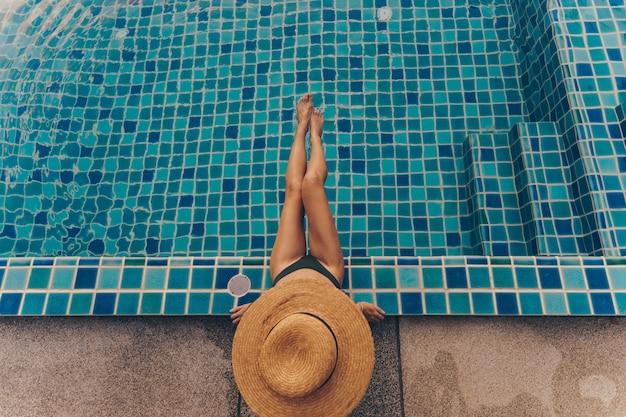 Achteraanzicht van sierlijke vrouw in zwembroek en hoed zitten bij het zwembad Gratis Foto