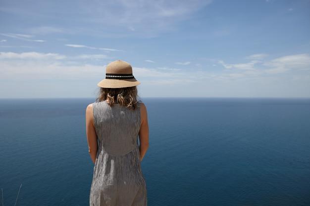 Achteraanzicht van slanke blonde jonge vrouw die jurk en strooien hoed draagt, genietend van zonnig weer buitenshuis, met uitzicht op uitgestrekte blauwe zee, op zoek naar afstand. mensen, natuur, zeegezicht, zomer en reizen Gratis Foto