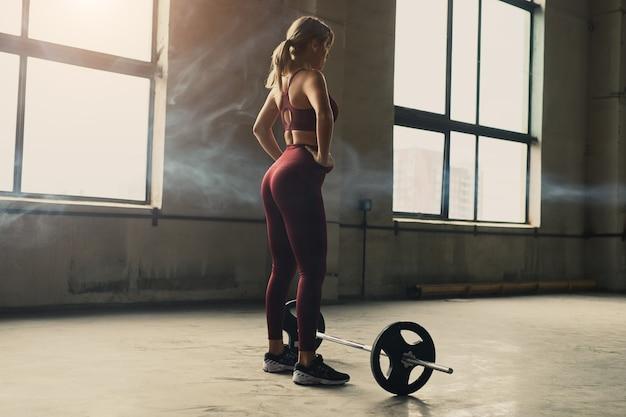 Achteraanzicht van sterke vrouwelijke atleet met handen op taille staande in de buurt van barbell tijdens gewichtheffen training in de sportschool Premium Foto
