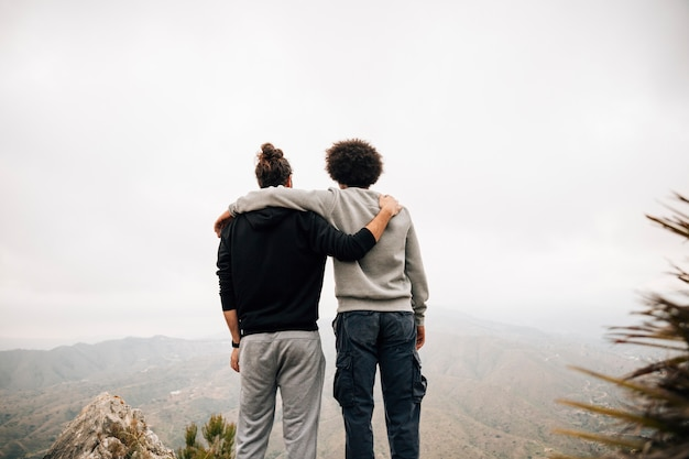 Achteraanzicht van twee mannelijke wandelaar met uitzicht op de bergen Gratis Foto