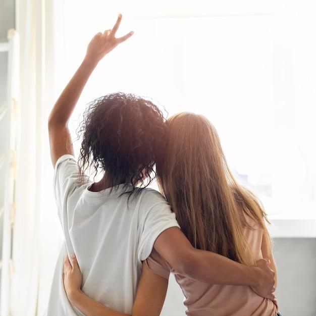 Achteraanzicht van twee vriendinnen knuffelen voor het raam Gratis Foto